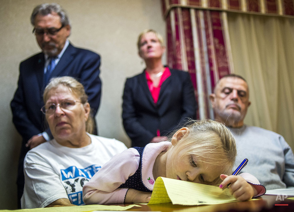 Lyla McCallun, 4, formerly of Flint, draws on a sheet of paper while sitting on the lap of her grandmother, Flint resident Jacqueline Pemberton, as they wait for the start of a press conference, announcing the filing of a potential class action lawsuit against both city and state government officials on Monday, Nov. 16, 2015 at the Holiday Inn Express in Flint. Pemberton is one of six others listed as plaintiffs in the lawsuit, which claims that these government officials violated constitutional rights providing lead-tainted water to residents, which lead to alleged developing health issues, including hair loss, depression and auto-immune disorders. (Jake May /The Flint Journal-MLive.com via AP) 