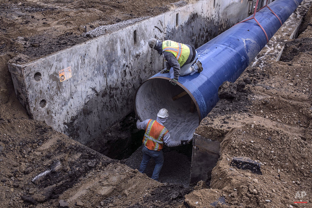 In this photo taken Dec. 18, 2015, a construction crew works on laying pipe for the Karegnondi Water Authority pipeline along Norway Lake Road in Lapeer, Mich. About 1,200 workers are taking advantage of the relatively mild winter to build the final portion of a new pipeline to bring water from Lake Huron to communities including Flint. (Sean Proctor/The Flint Journal-MLive.com via AP) 