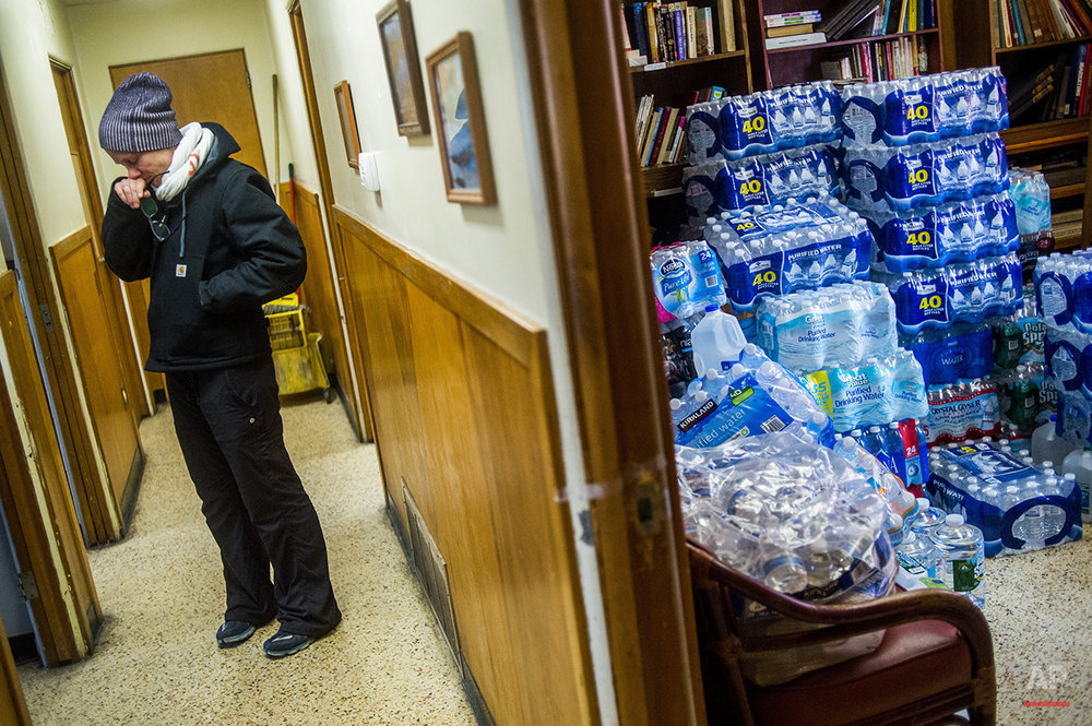 St. Clair Shores resident Terra Castro wipes away tears as she takes a moment to reflect on the state of emergency in Flint while dropping off more than 500 cases of bottled water with about 20 Detroit-based volunteers on Saturday, Jan. 16, 2016, at Mission of Hope on Flint, Mich.'s north side. President Barack Obama has signed an emergency declaration for Flint, Michigan, that clears the way for federal aid to the city undergoing a drinking water crisis. (Jake May/The Flint Journal-MLive.com via AP) 