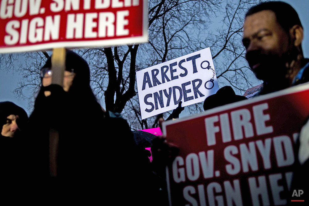 More than 150 activists protest outside of City Hall to protest Michigan Gov. Rick Snyder's handling of the water crisis, Friday, Jan. 8, 2016 in Flint. Mich. (Jake May/The Flint Journal-MLive.com via AP) 