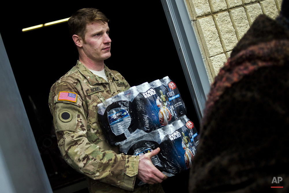 Michigan National Guard Staff Sgt. Stephen Robel helps carry a case of water to the vehicle of Flint resident Karand Houston as the first seven Michigan National Guard soldiers arrive on the ground at fire stations on Wednesday, Jan. 13, 2015 throughout Flint, assigned by Gov. Rick Snyder on Tuesday to help distribute water and relieve residents in relation to the Flint water crisis. Safe drinking water has not flowed from many Flint faucets for almost two years after the state-run city switched its source to the highly corrosive Flint River and failed to treat it properly to protect lead from leaching into it. (Jake May/The Flint Journal-MLive.com via AP)