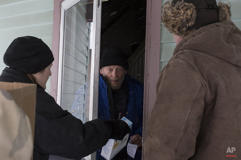 Volunteers go door to door in Flint Neighborhoods distributing water filters, replacement cartridges, and bottled water on Tuesday, Jan. 12, 2016. The volunteers were escorted by State Police and Genesee Country Sheriff's deputies. Safe drinking water has not flowed from many Flint faucets for almost two years after the state-run city switched its source to the highly corrosive Flint River and failed to treat it properly to protect lead from leaching into it. (Conor Ralph/The Flint Journal-MLive.com via AP) 