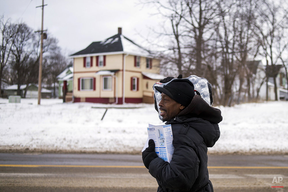 Flint resident Charles Chatmon carries a free water filter and case of water away from a fire station where members of the Michigan National Guard helped distribute supplies to aid in the city's water crisis, on Wednesday, Jan. 13, 2016, in Flint, Mich. Flint's tap water became contaminated with too much lead after the city switched its water supply in 2014 to save money while under state financial management. (Jake May/The Flint Journal-MLive.com via AP)