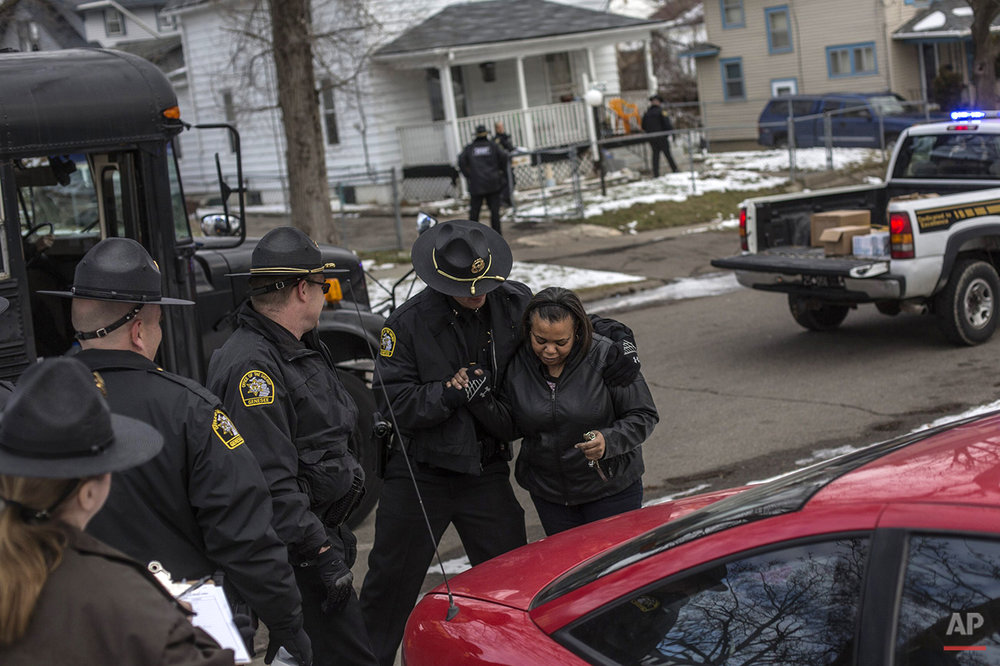 Colette Brown is helped by a police officer after expressing gratitude upon hearing that the Genesee County Sheriff's office and a work detail of people sentenced to community service were handing out water filters and gallons of water to residents of Flint's north side on Thursday, Jan. 7, 2016, in Mich. Michigan's governor pledged additional state assistance Thursday for the southeastern Michigan city of Flint as it deals with elevated lead levels in its drinking water, but he provided little detail about what additional help and money would be provided. (Sean Proctor /The Flint Journal-MLive.com via AP)