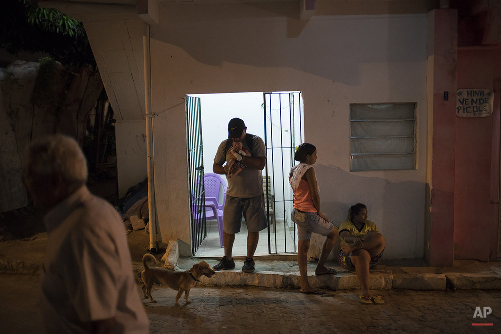 In this Jan. 26, 2016 photo, Daniele Ferreira dos Santos, center right, stands outside her house as her ex-husband holds their son Juan Pedro, who was born with microcephaly, outside her house in Recife, Pernambuco state, Brazil. Almost from birth, Pedro cried ceaselessly, as do many babies with microcephaly. Her husband was annoyed by the baby's constant fussing, which distracted him from his television show, she said, and then within weeks of the baby's arrival, left the house with the family's flat screen TV. (AP Photo/Felipe Dana)