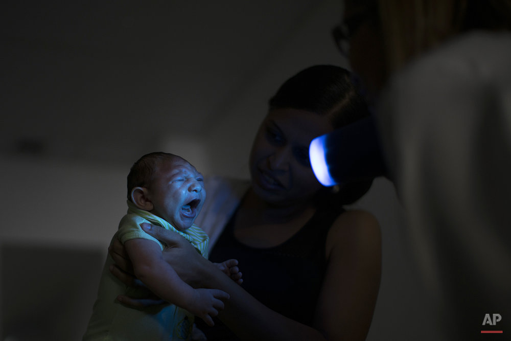 Daniele Ferreira dos Santos holds her son Juan Pedro as he undergoes visual exams at the Altino Ventura foundation in Recife, Pernambuco state, Brazil, Thursday, Jan. 28, 2016. Santos was never diagnosed with Zika, but she blames the virus for her son's defect and for the terrible toll it has taken on her life (AP Photo/Felipe Dana)
