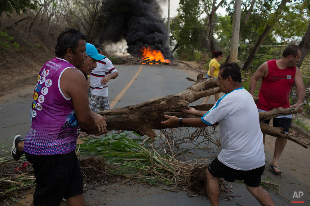 In this Nov. 21, 2015 photo, men place a large tree branch to use as a burning barricade while they protest for the lack of drinking water, in Colatina, Brazil. Nearly a month after a dam at a nearby Samarco iron mine burst, the effects of the disaster continue to ripple outward, affecting hundreds of thousands of people in two states, compromising the drinking water source for residents of cities in Minas Gerais and Espirito Santo states. (AP Photo/Leo Correa)