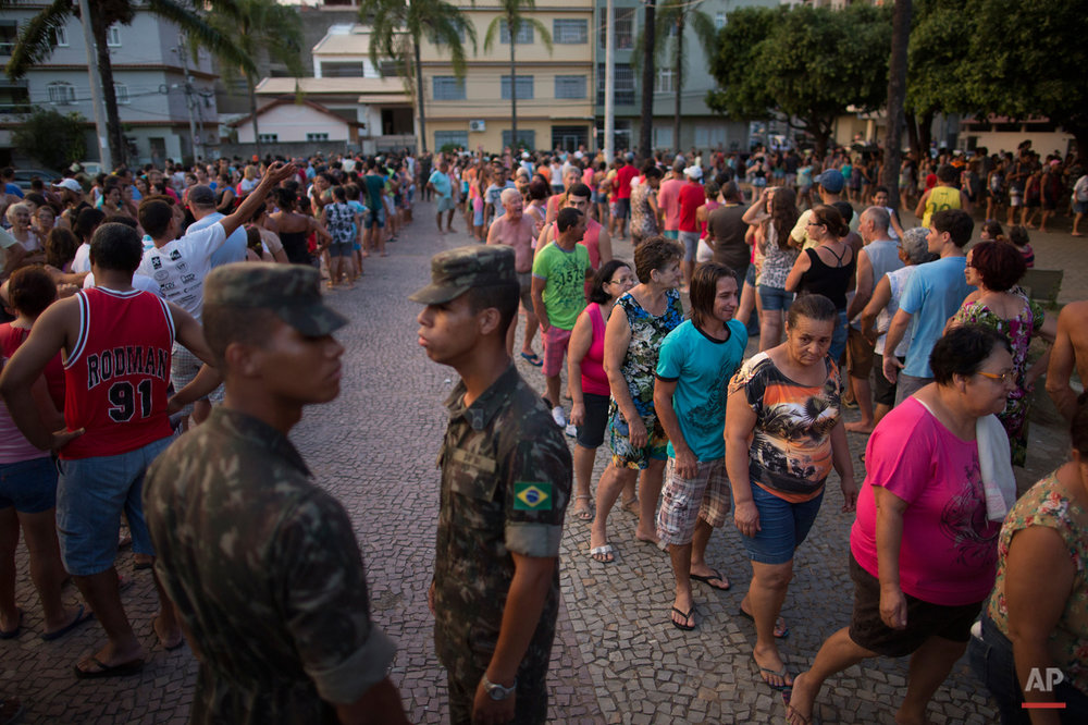 In this Nov. 21, 2015 photo, residents stand in line at a free water distribution site, weeks after a dam burst at the Samarco iron mine, causing mudslides and contaminated the area's drinkable water supplies, in Colatina, Brazil. The bottled water is provided by Samarco, which is jointly owned by mining giants Vale of Brazil and Australiaís BHP Billiton. (AP Photo/Leo Correa)