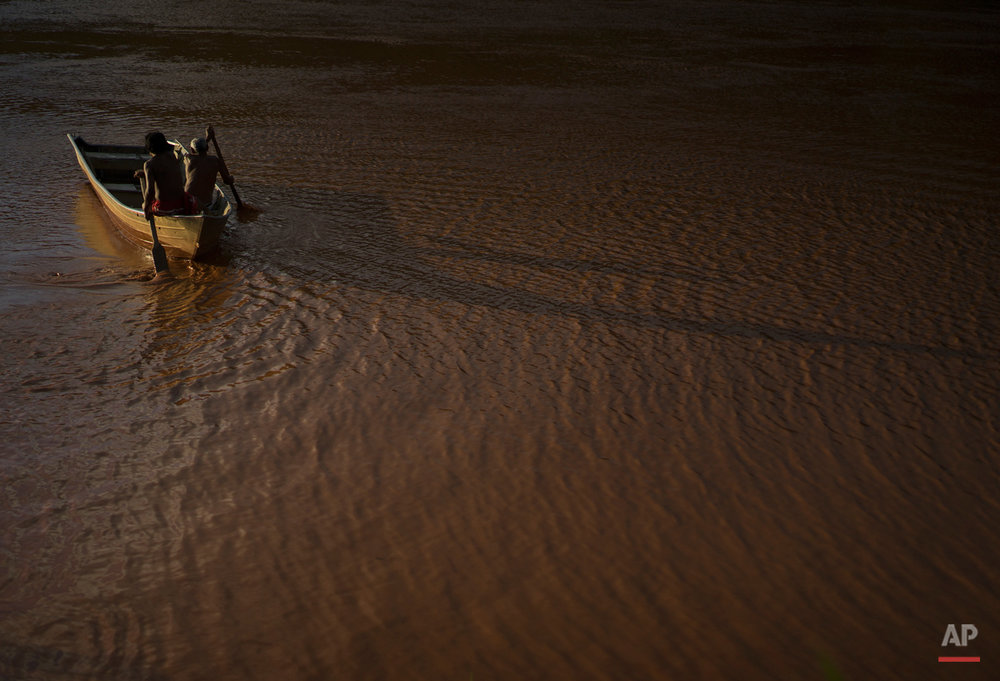 In this Nov. 22, 2015 photo, Ererre, left center, and Jose Cecilio Damasceno, both of the Krenak people, row their boat on the Doce River, polluted by a mix of residues from a dam that burst in early November, in Resplendor, Minas Gerais state, Brazil. The disaster threatens their traditional way of life as an indigenous people who live along the Doce River.  (AP Photo/Leo Correa)