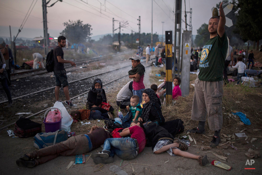 Syrian refugees wait near the border railway station of Idomeni, northern Greece, in order to be allowed by the Macedonian police to cross the border from Greece to Macedonia, Tuesday, Aug. 25, 2015. Greece has been overwhelmed this year by record numbers of migrants who have been arriving on a number of Greek islands.(AP Photo/Santi Palacios)
