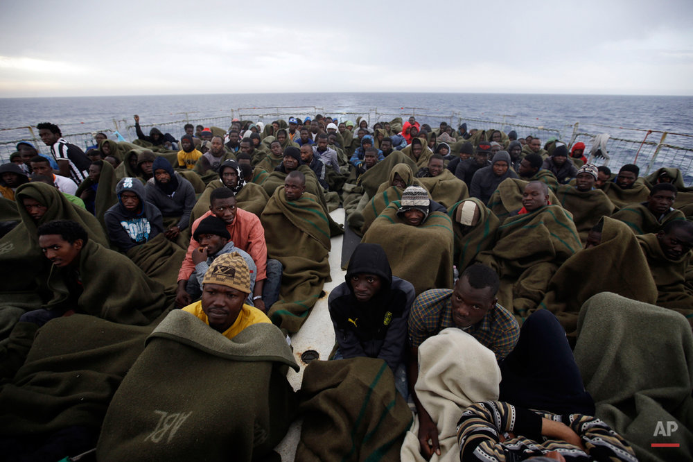 Migrants sit on the deck of the Belgian Navy vessel Godetia after they were saved at sea during a search and rescue mission in the Mediterranean Sea off the Libyan coasts, Wednesday, June 24, 2015. Hundreds of migrants were rescued by the Godetia, which is part of a EU Navy vessels fleet taking part in the Triton migrants rescue operation. (AP Photo/Gregorio Borgia)