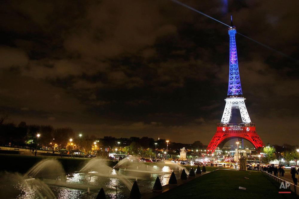"The illuminated Eiffel Tower shines in the bright colors of the French national flag, the ""Tricolor,"" in Paris, France, Nov. 16, 2015. At least 129 people were killed and 350 people injured in a series of terrorist attacks in Paris on the night Nov. 13, 2015. (Malte Christians/picture-alliance/dpa/AP Images via AP)"