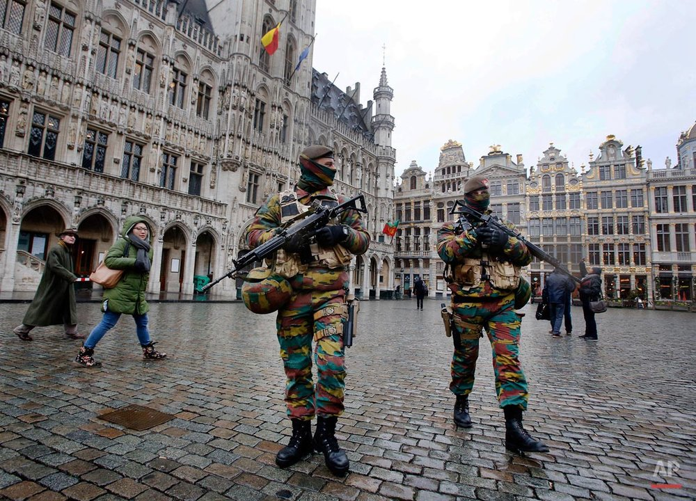 Belgium police officers patrol the Grand Place in central Brussels, Belgium, Tuesday, Nov. 24, 2015. The lockdown has closed the capital's subways and schools. Officials have recommended that popular shopping districts be shuttered and advised people to avoid public places since they could be targeted by terrorists. (AP Photo/Michael Probst)