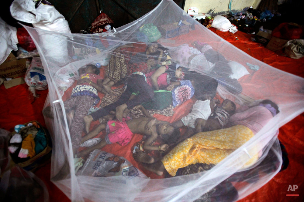 Ethnic Rohingya women and children sleep under mosquito net at a temporary shelter in Langsa, Aceh province, Indonesia, Sunday, May 17, 2015. Boats filled with more than 2,000 desperate and hungry people landed in Indonesia, Malaysia and Thailand, and thousands more migrants are believed to be adrift at sea after a crackdown on human traffickers prompted captains and smugglers to abandon their human cargo. (AP Photo/Binsar Bakkara)