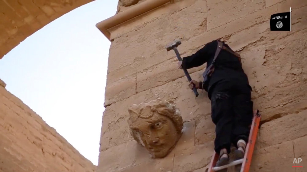 In this image made from a militant video posted on YouTube on Friday, April 3, 2015, which has been verified and is consistent with other AP reporting, a militant hammers away at a face on a wall in Hatra, a large fortified city recognized as a UNESCO World Heritage site, 110 kilometers (68 miles) southwest of Mosul, Iraq. The Islamic State group's attacks on these famed archaeological treasures are partially motivated by the group's hostility to non-Islamic and pre-Islamic cultures. But some antiquities authorities have charged that the destruction is a partial cover for the militants' lucrative business in selling looted artifacts on the black market. (Militant video via AP)