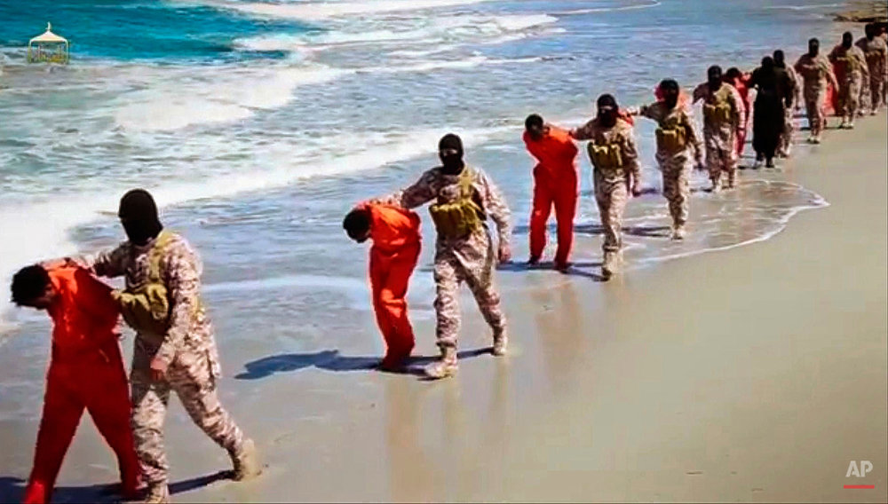 EDS NOTE: GRAPHIC CONTENT - This undated image made from a video released by Islamic State militants, Sunday, April 19, 2015, appears to show the killing of a group of captured Ethiopian Christians in Libya. The 29-minute video released online purportedly shows two groups of captives. It says one group is held by an IS affiliate in eastern Libya and the other by an affiliate in the south. A masked fighter delivers a long statement before the video switches between footage that purportedly shows the captives in the south being shot dead and the captives in the east being beheaded on a beach. (Militant video via AP)