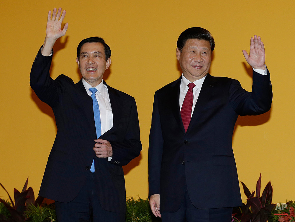 Chinese President Xi Jinping, right, and Taiwanese President Ma Ying-jeou, left, wave to the media at the Shangri-la Hotel on Saturday, Nov. 7, 2015, in Singapore. The two leaders shook hands at the start of a historic meeting, marking the first top level contact between the formerly bitter Cold War foes since they split amid civil war 66 years ago. (AP Photo/Wong Maye-E)