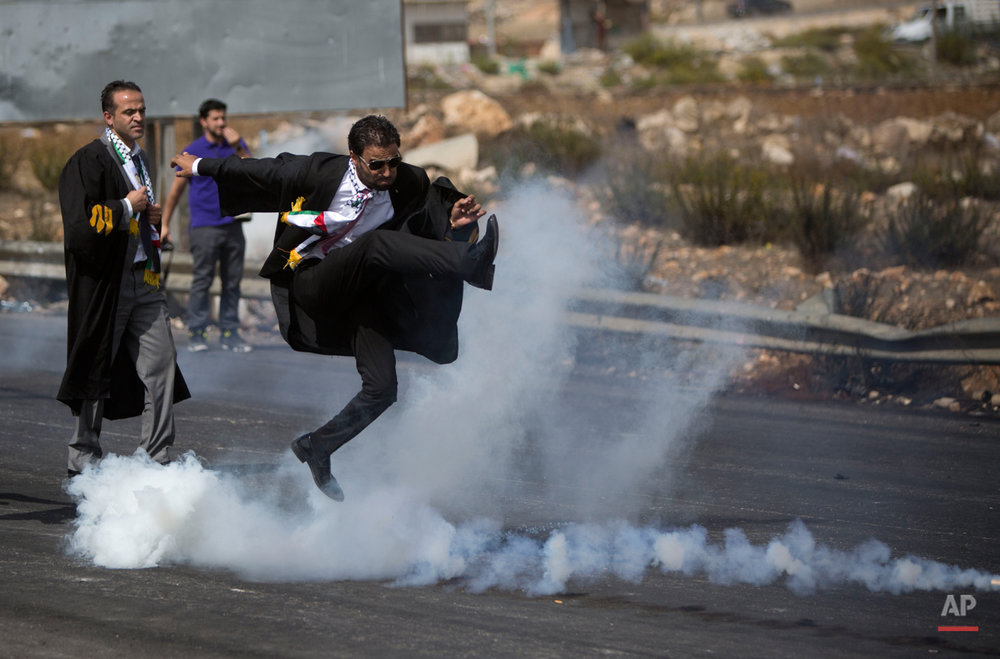 A lawyer wearing his official robes kicks a tear gas canister back toward Israeli soldiers during a demonstration by scores of Palestinian lawyers called for by the Palestinian Bar Association in solidarity with protesters at the Al-Aqsa mosque compound in Jerusalem's Old City, near Ramallah, West Bank, Monday, Oct. 12, 2015. (AP Photo/Majdi Mohammed)