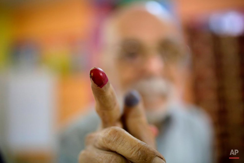 Egyptian voter Abdel Moneam Kandil, 80, shows his inked finger after he voted at a polling station for the runoff to the first round of the parliamentary elections in Giza, just outside of Cairo, Egypt, Wednesday, Oct. 28, 2015. (AP Photo/Amr Nabil)