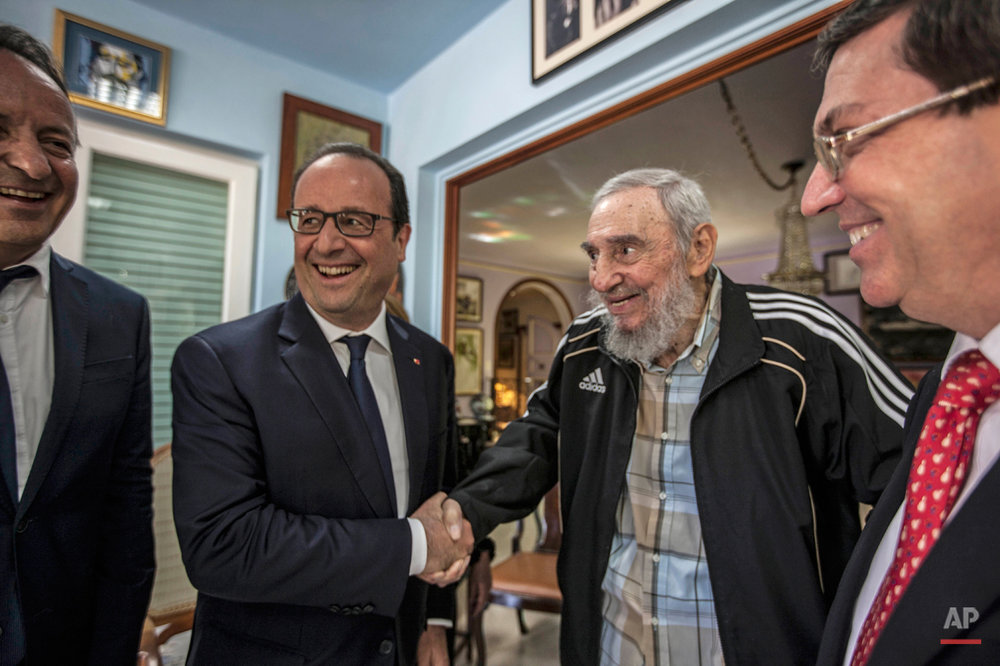 Cuba's former leader Fidel Castro, second right, shakes hands with French President Francois Hollande, while accompanied by Cuba's Foreign Minister Bruno Rodriguez, right, and an unidentified person, left, in Havana, Cuba, Monday, May 11, 2015. Hollande is the first French leader to visit the island nation in more than a century and also the first Western leader to travel to Cuba since the surprise announcement in December of a rapprochement between Washington and Havana. (AP Photo/Alex Castro)