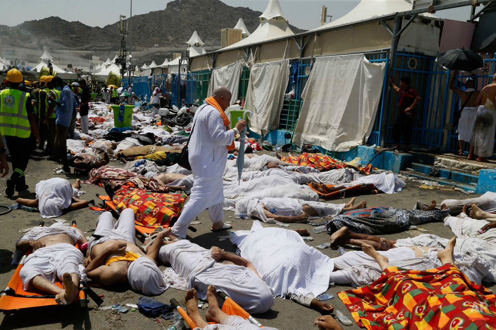 A muslim pilgrim walks through the site where dead bodies are gathered in Mina, Saudi Arabia during the annual hajj pilgrimage on Thursday, Sept. 24, 2015. Hundreds were killed and injured. The crush happened in Mina, a large valley about five kilometers (three miles) from the holy city of Mecca that has been the site of hajj stampedes in years past. (AP Photo)