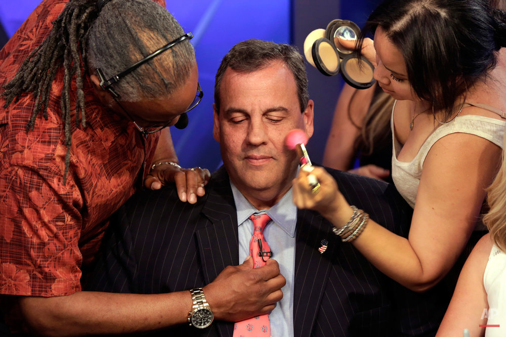 "Republican presidential candidate New Jersey Gov. Chris Christie gets his microphone and make-up prepared for his appearance on ""The Five"" television program, on the Fox News Channel, in New York, Wednesday, July 22, 2015. (AP Photo/Richard Drew)"