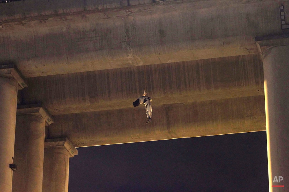 An unidentified dead man hangs from his waist under an overpass in the southern part of Mexico City, early Monday, Oct. 19, 2015. The man was found wrapped in white bandages and a cap, or hoodie, was covering his head. This is the first time a body appeared on a bridge or overpass in Mexico City, a common practice among criminal gangs fighting for control of turf in other regions of Mexico. Mexico City authorities have repeatedly stated that the capital is safe from the wave of violence that continues to affect many parts of the country. (AP Photo/Jair Cabrera)