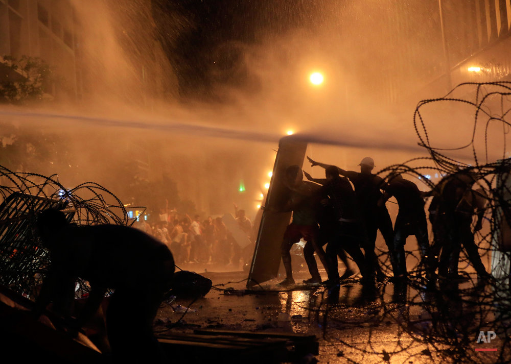 Lebanese activists hold up a makeshift shield as they are sprayed by riot police using water cannons during a protest against the ongoing trash crisis, in downtown Beirut, Lebanon, Sunday, Aug. 23, 2015. Lebanese riot police fired several rounds of tear gas and water cannons for the second consecutive day in downtown Beirut as they battled protesters with batons and stones _ a marked escalation of mass demonstrations against an ongoing trash crisis. (AP Photo/Hassan Ammar)