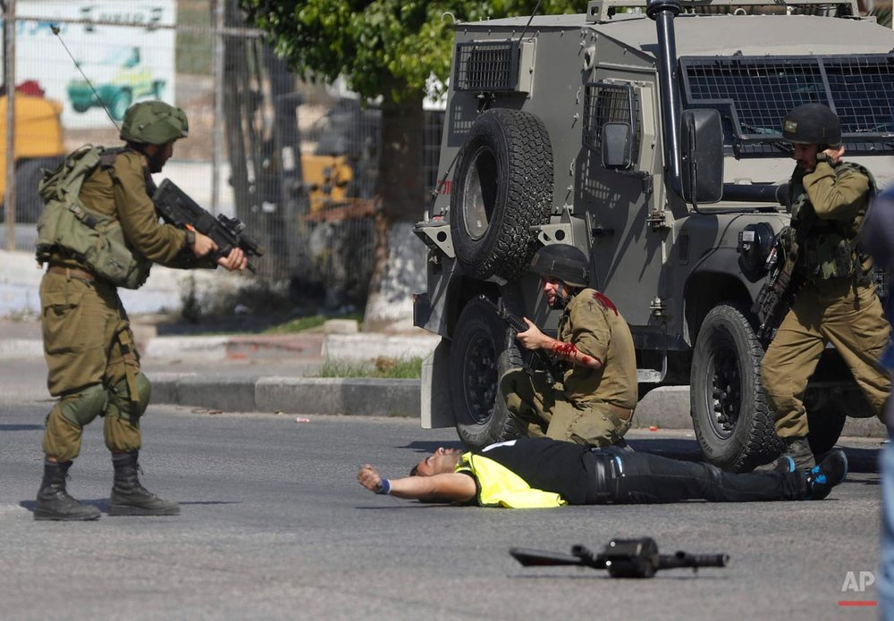 "An Israeli soldier shoots a Palestinian holding a knife after he stabbed another Israeli soldier, seen kneeling, during clashes in Hebron, West Bank Friday, Oct. 16, 2015. The Palestinian man wearing a yellow ""press"" vest and a T-shirt identifying him as journalist stabbed and wounded an Israeli soldier in the West Bank city of Hebron before being shot dead by troops, the latest in a monthlong spate of attacks. (AP Photo/Nasser Shiyoukhi)"
