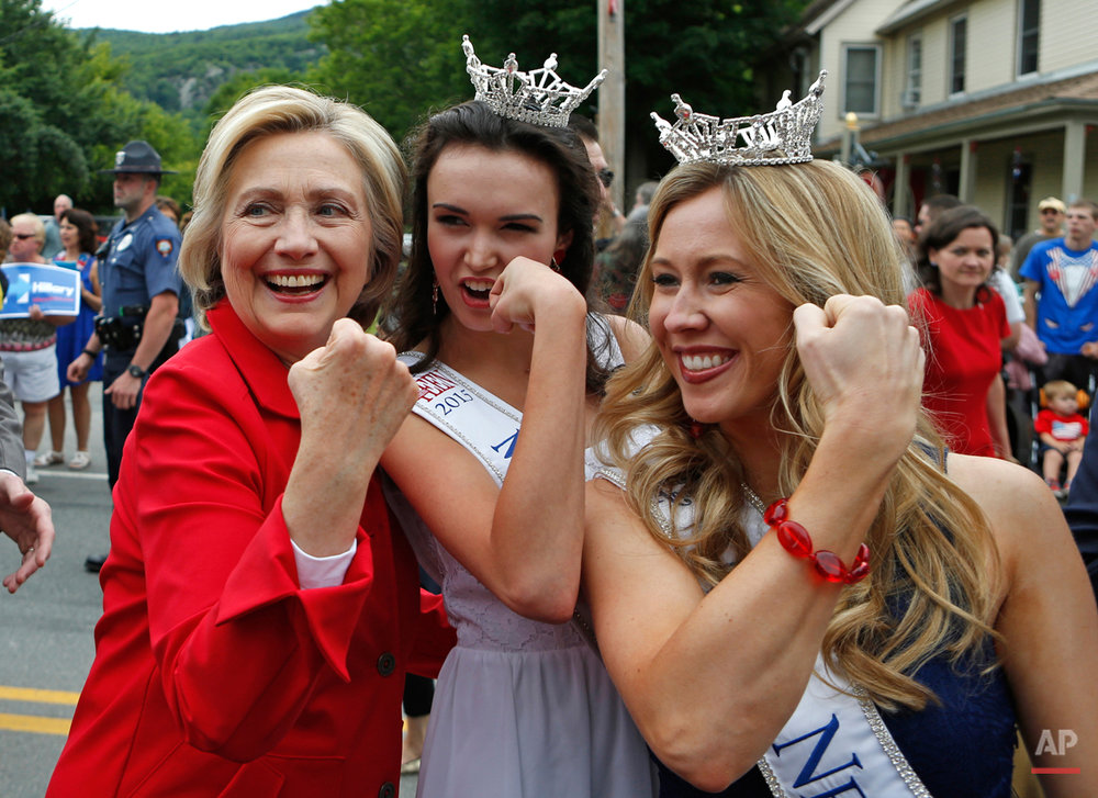 Democratic presidential candidate Hillary Rodham Clinton flexes her muscles with Miss Teen New Hampshire Allie Knault, center, and Miss New Hampshire Holly Blanchard, during a Fourth of July parade, Saturday, July 4, 2015, in Gorham, N.H. (AP Photo/Robert F. Bukaty)