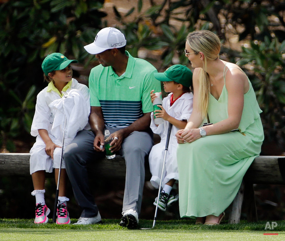 Lindsey Vonn sits with Tiger Woods and his children Sam and Charlie during the Par 3 contest at the Masters golf tournament Wednesday, April 8, 2015, in Augusta, Ga. (AP Photo/David J. Phillip)