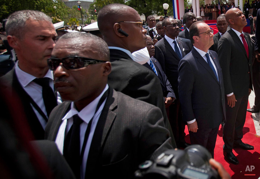 In this May 12, 2015, photo, bodyguards stand around France's President Francois Hollande, second from right, and Haiti's President Michel Martelly, right, during a flower laying ceremony at the statue of Haiti's Revolution leader Toussaint Louverture at the National Palace in Port-au-Prince, Haiti. Hollande is making the second visit ever by a sitting president of France to its once prized possession of Haiti, where bountiful resources and brutal plantation slavery made it the European nation's most profitable colony some 250 years ago. (AP Photo/Dieu Nalio Chery)