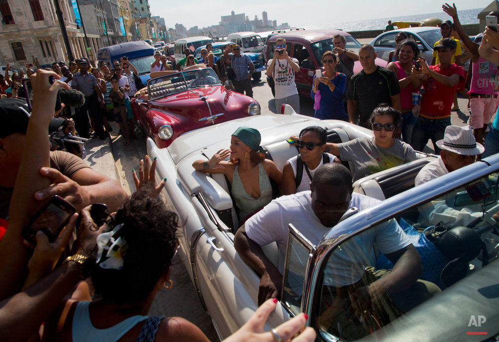 In this May 29, 2015, photo, fans take photographs of pop artist Rihanna, wearing a green scarf, as she is transported in an American classic car, after a photo shoot with photographer Annie Leibovitz at a building on the Malecon, in Havana, Cuba. (AP Photo/Desmond Boylan)