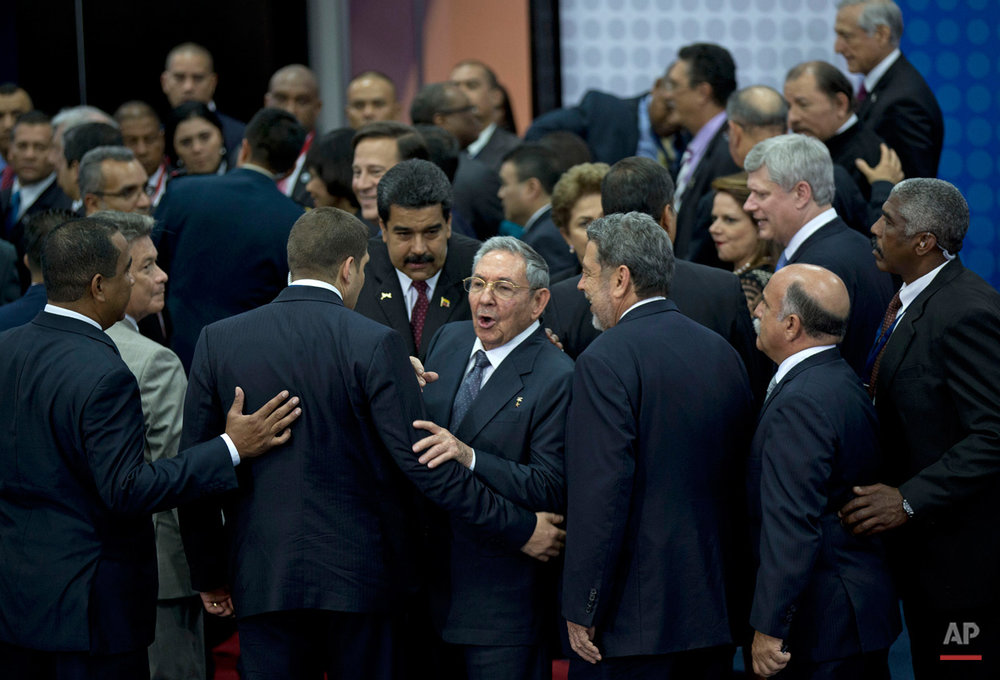 In this April 11, 2015, photo, Cuba's President Raul Castro talks at reporters before turning to leave the staging area of the official group photo of the VII Summit of the Americas in Panama City, Panama. Castro is flanked by his personal assistant and grandson, Raul Guillermo Rodriguez Castro, Venezuela's President Nicolas Maduro, and Prime Minister of Saint Vincent and the Grenadines Ralph Gonsalves. Castro and U.S. President Barack Obama held their first formal meeting in more than half a century on Saturday, clearing the way for a normalization of relations. (AP Photo/Ramon Espinosa)