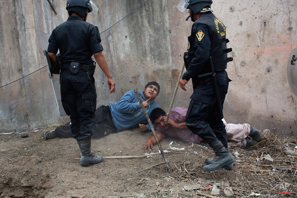 In this May 19, 2015, photo, riot police detain men during a land eviction in Lima Peru. On Monday hundreds of people squatted on land that according to the Ministry of Culture is an archaeological site. (AP Photo/Rodrigo Abd)
