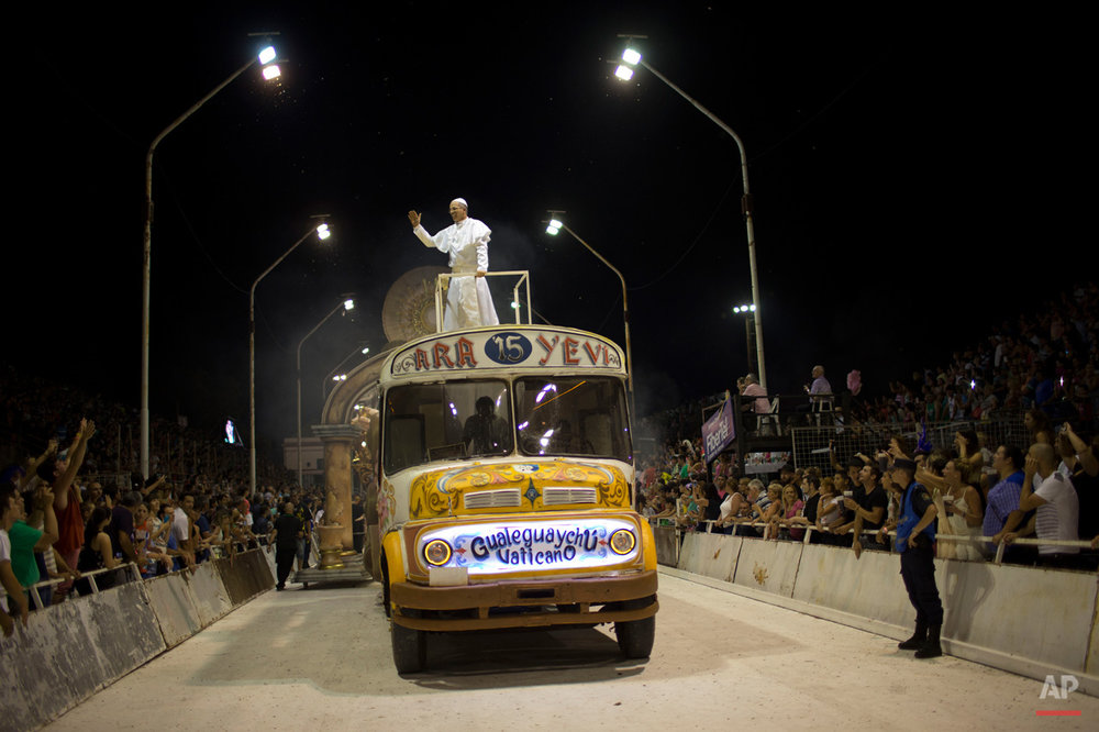 In this Jan. 11, 2015, photo, Roman Figun, a local lawyer, performs the role of Pope Francis with the Ara Yevi samba school as he stands on a bus representing his humble arrival to the Vatican during carnival celebrations in Gualeguaychu, Argentina. Ara Yevi, one of the three samba schools performing this year, used Pope Francis as their central theme. (AP Photo/Natacha Pisarenko)
