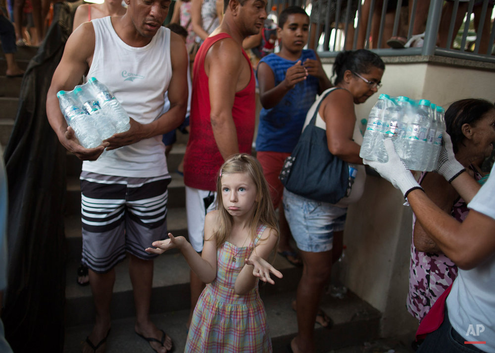 In this Nov. 21, 2015, photo, a girl questions why the man standing next to her was allowed to step ahead of her in a line for free water, at a distribution site, in Colatina, Brazil. Residents were queuing day and night for the bottles of water. (AP Photo/Leo Correa)