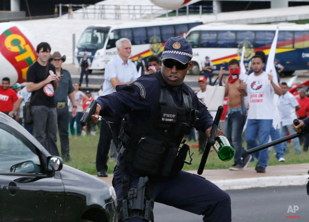 In this April 7, 2015, photo, a military police officer aims his gun to a demonstrator during a protest in Brasilia, Brazil. The officer had picked up a bottle that was thrown towards them but did not fire his gun and backed away. Thousands of workers have staged rallies in 12 cities across Brazil to protest against a proposed law that would allow companies to outsource their labor force. (AP Photo/Eraldo Peres)