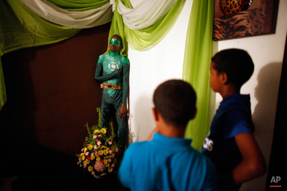 In this Feb. 15, 2015, photo, two boys attend the wake of Renato Garcia, dressed as fictional superhero the Green Lantern and propped up against a wall in his sister's apartment, in San Juan, Puerto Rico. Garcia's sister explained that she and her brother never discussed funeral wishes, but neighbors and friends suggested dressing him as the comic book superhero. (AP Photo/Ricardo Arduengo)