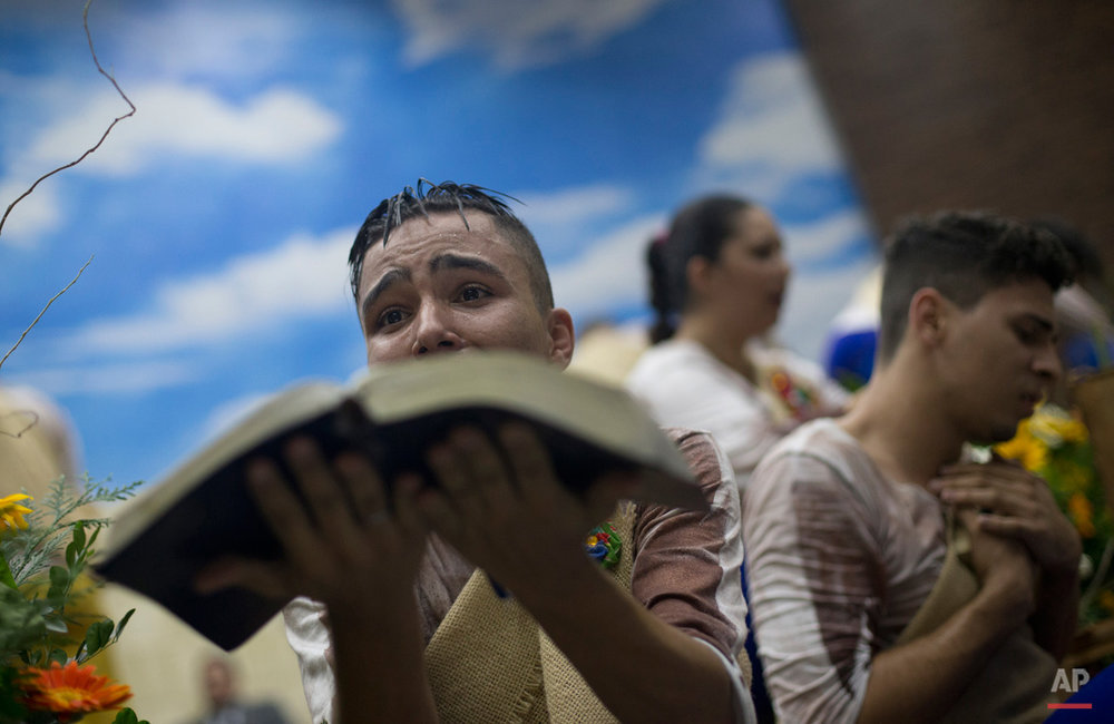 In this Sept. 7, 2015, photo, a young devotee performs while holding a Bible during a service at the Contemporary Christian Church in Rio de Janeiro, Brazil. At the Contemporary Christian Church, which celebrated its ninth anniversary and the opening of its ninth branch with a raucous, theatrical service, homosexuality is celebrated rather than stigmatized. (AP Photo/Silvia Izquierdo)