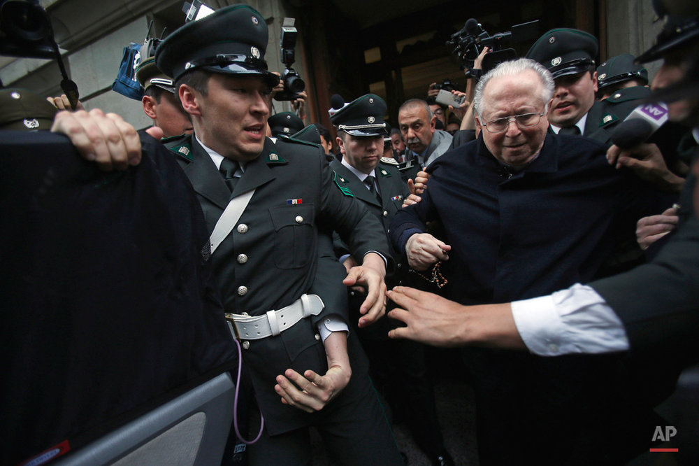 In this Nov. 11, 2015, photo, Fernando Karadima is escorted from a court, after testifying in a case that three of his victims brought against the country's Catholic Church in Santiago, Chile. The Vatican ordered Karadima to life of penance and prayer in 2011 for abusing three young boys. A local judge determined the abuse allegations were truthful but absolved Karadima because the time limit had expired for prosecution. The three victims who filed the suit accuse the Chilean Catholic church of a cover up. The church has rejected the accusation. (AP Photo/Luis Hidalgo)