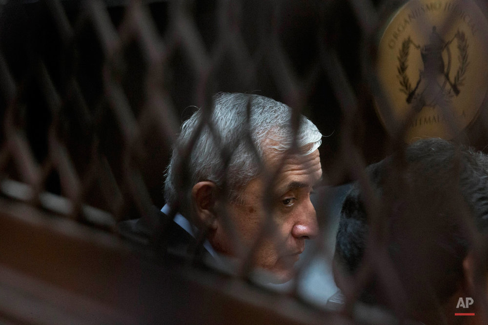 In this Sept. 8, 2015, photo, Guatemala's former president Otto Perez Molina, photographed through a window, sits in court for a third hearing on corruption allegations that led him to resign, in Guatemala City. The court is considering allegations that Perez Molina was involved in a scheme in which businesspeople paid bribes to avoid import duties through Guatemala's customs agency. (AP Photo/Esteban Felix)