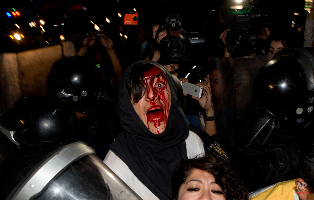 In this Feb. 26, 2015, photo, a protester injured in a scuffle with police shouts out his name as he and a woman are detained in Mexico City. The pair, and other protesters who had taken part in a march marking the fifth month of the disappearance of 43 students from a rural teachers college, clashed with police after they were prevented from entering the subway. (AP Photo/Eduardo Verdugo)