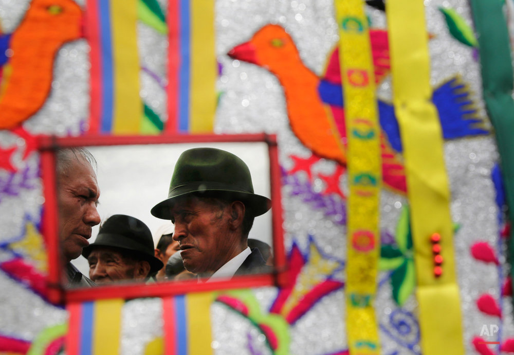 In this June 7, 2015, photo, men are reflected in†a mirror†on a†costume during the Corpus Christi dance in Pujili, Ecuador. Pujili dancers, their costumes representing the Andean condor, perform†on the streets of the town in a mix of Catholic beliefs and indigenous ancestral traditions of the harvest. (AP Photo/Dolores Ochoa)
