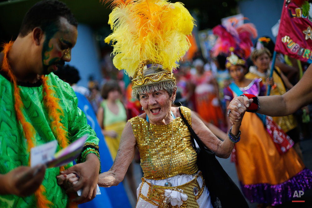 "In this Feb. 12, 2015, photo, an elderly patient in costume from the Nise de Silveira mental health institute dances during the institute's carnival parade, coined in Portuguese: ""Loucura Suburbana,"" or Suburban Madness, in the streets of Rio de Janeiro, Brazil. Patients, their relatives and institute employees held their parade one day before the official start of Carnival. (AP Photo/Silvia Izquierdo)"