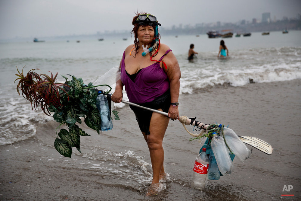 In this May 7, 2015, photo, Graciela Meneses poses for a picture on Fishermen's Beach, holding her self-made float, decorated with fake, plastic plants, after swimming in the Pacific Ocean in Lima, Peru. Graciela, 67, says she lost 39 kilograms (85 pounds) by exercising in the sea. (AP Photo/Rodrigo Abd)