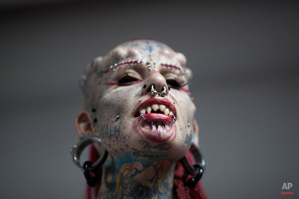 In this Jan. 29, 2015, photo, Mary Jose Cristerna, a Mexican known as The Vampire Woman, poses for the public to take portraits of her during the annual Venezuela Tattoo International Expo in Caracas, Venezuela. Tattoo artists from around the world are gathering for the four-day event that also includes under the skin implants and body piercing. (AP Photo/Ariana Cubillos)
