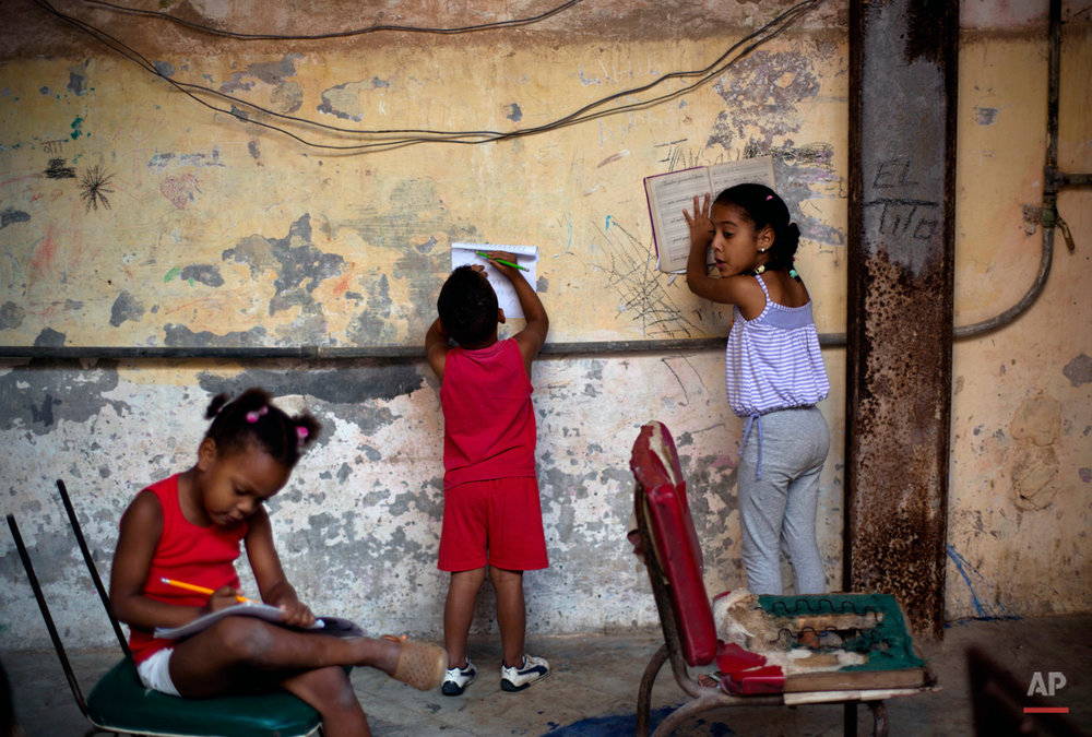 In this Jan. 19, 2015, photo, kids do their homework inside the courtyard of an apartment building in Havana, Cuba, Monday. Cuba has so far offered a guardedly positive reception to President Barack Obama's loosening of the trade embargo on Cuba, saying it welcomes the full package of new economic ties on offer, but it insists it will maintain its one-party political system and centrally planned economy. (AP Photo/Ramon Espinosa)