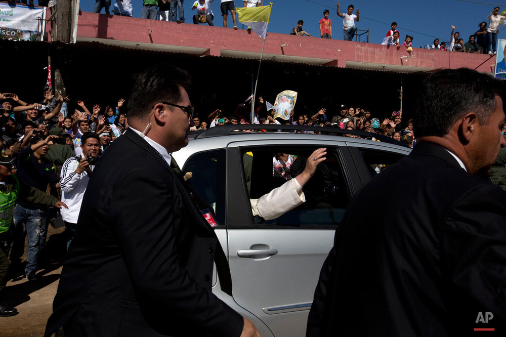 In this July 10, 2015, photo, Pope Francis waves from a car as he leaves Palmasola prison after visiting prisoners in Santa Cruz, Bolivia. Pope Francis wrapped up his pilgrimage to Bolivia with a visit to its notoriously violent and overcrowded Palmasola prison, where inmates have the run of the place, drugs are cheaper than on the street and money buys survival. (AP Photo/Rodrigo Abd)