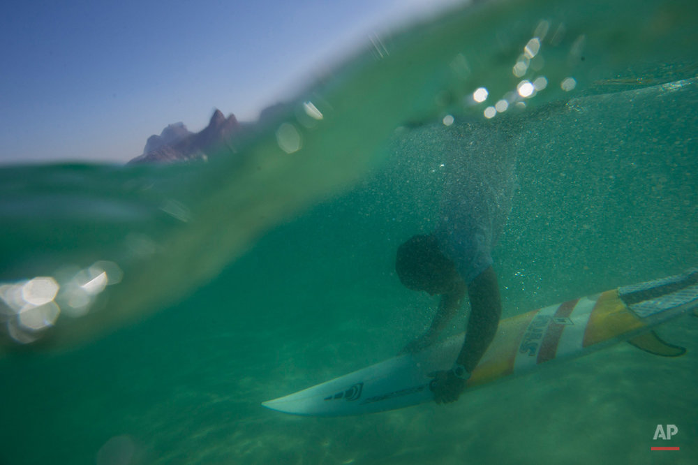 In this June 10, 2015, photo, Magno Neves dives with his board at Arpoador beach in Rio de Janeiro, Brazil. Neves, a 23-year-old from the Cantagalo slum, surfs nearly every day at the nearby Arpoador beach. (AP Photo/Felipe Dana)